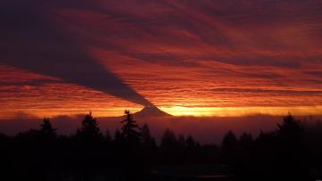 Beautiful photo of Mt Rainier casting an upwards shadow on the underneath of the clouds at sunset